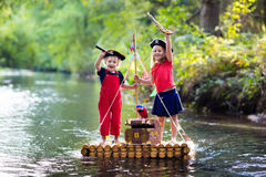 kids-playing-pirate-adventure-wooden-raft-dressed-costumes-hats-treasure-chest-spyglasses-swords-sailing-87028737
